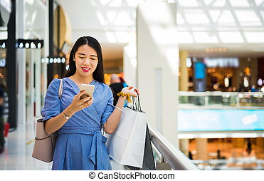 Girl using phone while doing shopping