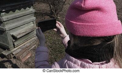 Girl using smartphone near bee hive