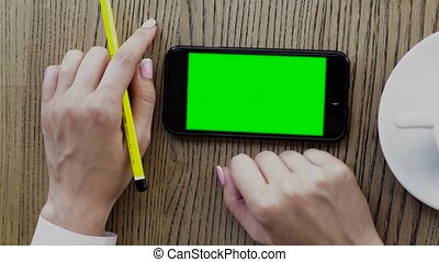Girl using smartphone on wood table. Hand touching black color smart phone with blank screen.