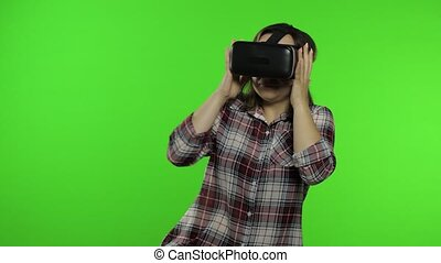 Young woman put on VR app headset helmet to play simulation scary game. Watching virtual reality 3D 360 horrible video. Isolated on chroma key background. Girl in VR goggles afraid, frightened