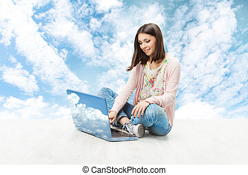 Girl using wireless laptop over sky background. Woman sitting and typing notebook computer.