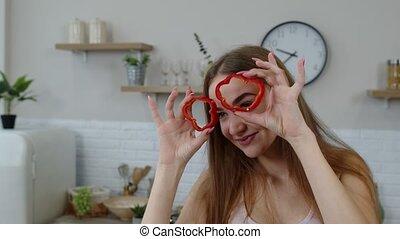 Girl vegan dancing holding fresh red slice of bell pepper on...