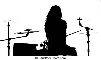 Girl vigorously plays the drums, her wand. White background. Silhouette