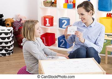 Girl visiting speech therapist - Little blond girl visiting...