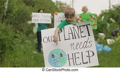 Girl volunteer holds encouraging protesting poster Our Planet Needs Help. Activists on background. Protests, chants. Forest park in cellophane bags, bottles. Plastic trash nature pollution. Recycle