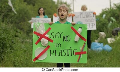 Girl child volunteer holds encouraging protesting poster Say No To Plastic. Activists on background. Protests, chants. Forest park in cellophane bags, bottles. Garbage trash nature pollution. Recycle