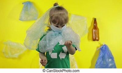 Junior girl activist in green t-shirt with recycle logo in plastic packages on her neck and head. Background with cellophane bags, bottles. Reduce trash plastic pollution. Save ecology environment