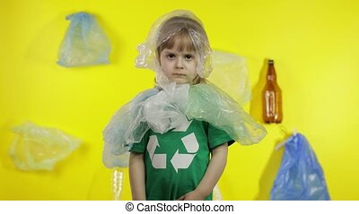 Sad girl activist in t-shirt with recycle logo in plastic packages on her neck and head. Background with cellophane bags, bottles. Reduce trash plastic pollution. Ecology environment preservation