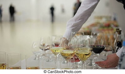 Girl waiter serves wine glasses to guests at the reception