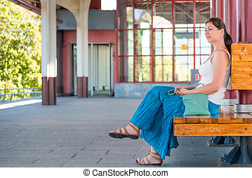 Girl waiting for the train at the station sitting on a bench