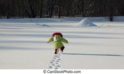 Girl walk by deep snow to forest on background, at sunny...