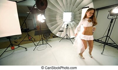 Girl walk inside photo studio, dances and blows kiss - Girl...