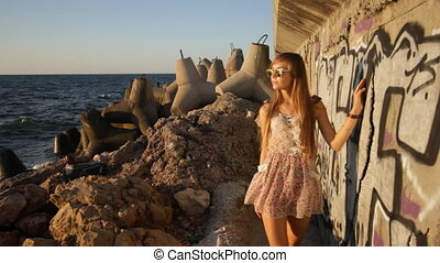 girl walking along graffiti wall near sea at sunset