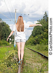 Girl walking along the old rails
