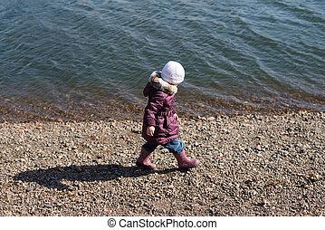 Girl walking along the riverbank