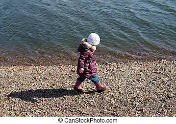 Girl walking along the riverbank