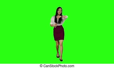 Girl walking along the road, looking at the clock starts to run. Green screen. Slow motion