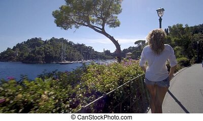 girl walking and looking down on the bay portofino italy