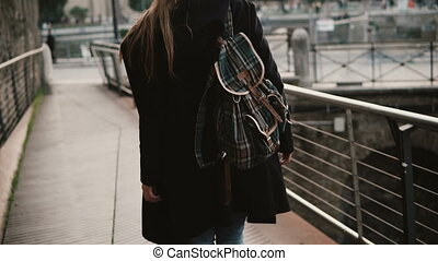 Girl walking around Rome, Italy, seeing over antique and...
