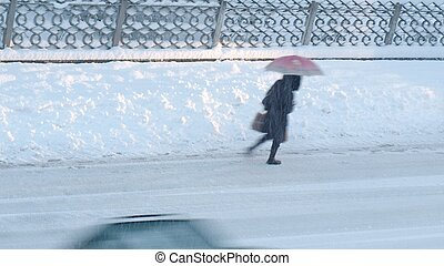 Girl walking in heavy snow - motion blur effect - (16:9 ratio)