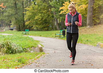 Girl walking in park with headphones - Young girl walking in...