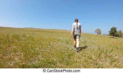 Girl walking in the field. Slow motion