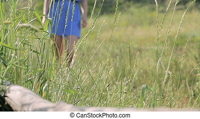 girl walking in the Park and touches the grass
