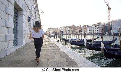 Girl walking in venice, Italy, seeing over antique and...