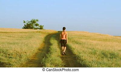 Girl walking on empty rural road