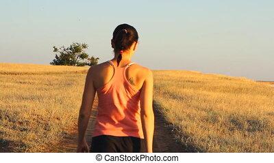 Girl walking on empty rural road fa