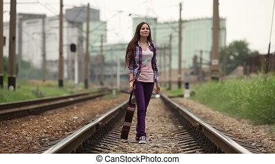 Girl walking on railway wish guitar - A girl in a shirt,...