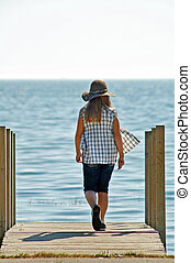 Girl Walking On Sunny Dock
