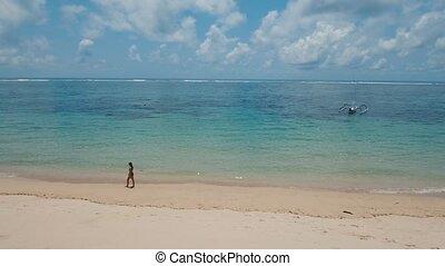 Girl walking on the beach. Bali, Indonesia.