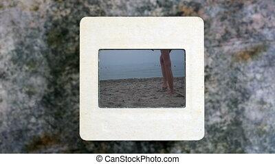 Girl walking on the beach on slide film