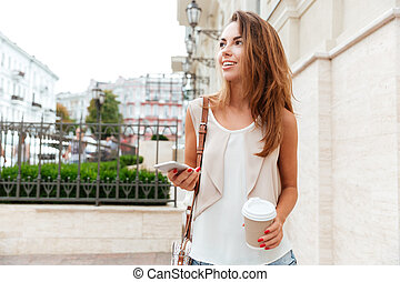 Girl walking on the street and drinking take away coffee