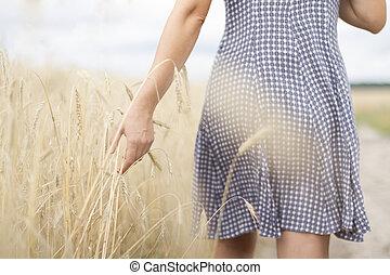 Girl walking on wheat field