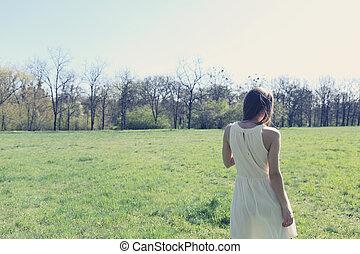 girl walking through a meadow