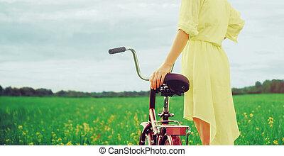 Girl walking with bike outdoor in summer