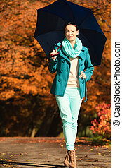 Girl walking with blue umbrella in autumnal park - Happiness...