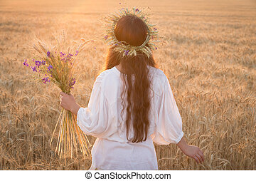Girl walking with sheaf on wheat field at sunset