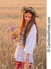 Girl walking with sheaf on wheat field at sunset, touching the e