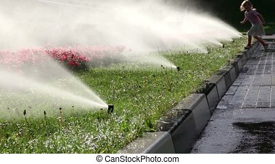 Girl walks along the flowerbed and wets her hands in water,...