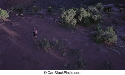 Girl walks along the Rim of East Fork Shafer Canyon near...