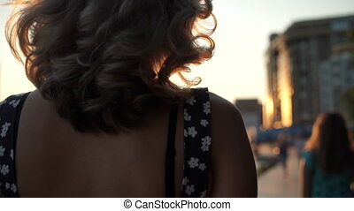 Girl walks at sunset in the city