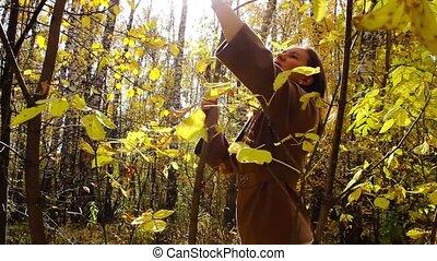 Girl walks in autumn forest