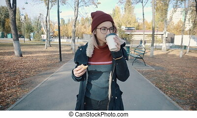Girl walks in the Park and eating a burger and drink coffee. Girl in a jacket and hat