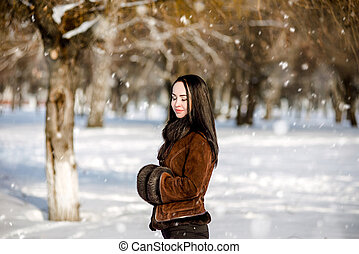 Girl walks in the park in winter