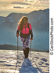 Girl walks in the snow during an alpine trek
