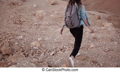 Girl walks on a desert sheer drop. Slow motion. Young woman...