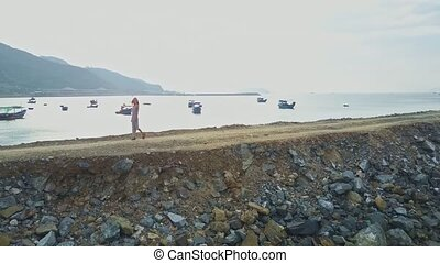 Girl Walks on Ground Ocean Dyke against Boats and City